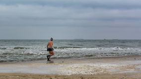 Icebathing man on Baltic beach. Stock Photo