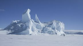 Iceberg. Tourist looking at an iceberg frozen solid in the sea ice on Antarctica Royalty Free Stock Images