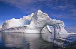 Iceberg with an Arch, Antarctica. Iceberg with a natural arch, reflected in the water, in the still, quiet beauty of Antarctica, at the bottom of the world Royalty Free Stock Photos