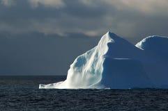 Iceberg bianco-blu Sunlit con il cielo scuro Immagini Stock Libere da Diritti
