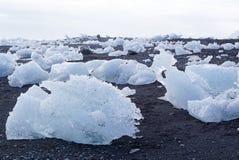 Iceberg on the black rock beach Stock Photos