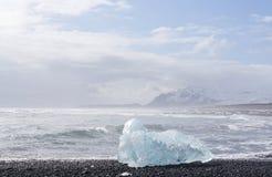 Iceberg on the black rock beach Stock Photography