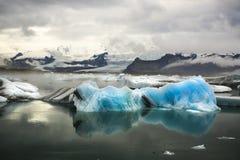 Iceberg blu con il ghiacciaio e le montagne Immagine Stock