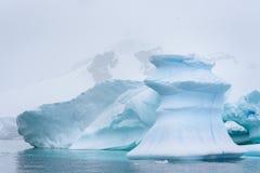 Iceberg bonito do azul de turquesa que flutua no ant?rtico, contra um fundo nevoento imagem de stock royalty free