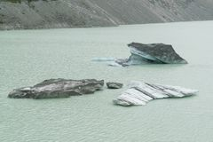 Iceberg breaking from glacier over water lake stock photography