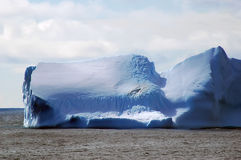 Iceberg in calm waters Stock Images