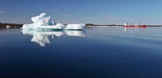 Iceberg and cargo ship Stock Photography