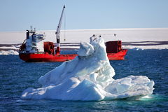 Iceberg and cargo ship Royalty Free Stock Images