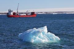 Iceberg and cargo ship Stock Photos