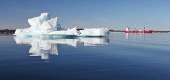 Iceberg and cargo ship Stock Image