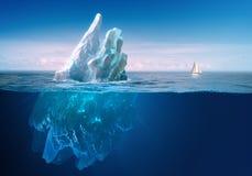 Iceberg debajo del cielo azul con la línea subacuática de la parte y de agua fotografía de archivo libre de regalías