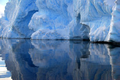 Iceberg detail reflected in the sea. Crisp reflection of a blue iceberg Royalty Free Stock Images