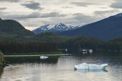 Iceberg di galleggiamento, due barche e montagna nei precedenti con il cielo nuvoloso Fotografie Stock