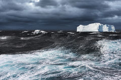Iceberg Drifting in Ocean. Big Iceberg Drifting in Stormy Ocean Royalty Free Stock Photo