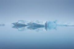 Iceberg e le loro riflessioni in una nebbia, Jokulsarlon, Islanda Fotografia Stock