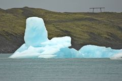 Iceberg extraño delante de una colina Imagenes de archivo
