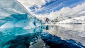 Iceberg floats in Andord Bay on Graham Land, Antarctica. In rare sunshine during spring Royalty Free Stock Image