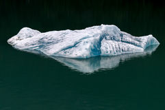Iceberg floats in the waters of Alaska. This single iceberg floats with deep blue colors in the green waters of Alaska Stock Photography