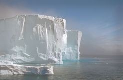 Iceberg in the Fog, Antarctica. Iceberg in the lifting fog, with turquoise water, in the still, quiet beauty of Antarctica