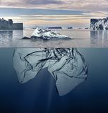 Iceberg of garbage plastic floating in ocean with greenland back stock photo