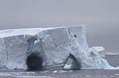 Iceberg grande en dos cuevas en el antártico
