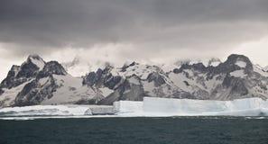 Iceberg Graveyard. Large tabular icebergs against the background of a South Georgian mountain range stock photo