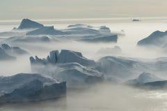 Iceberg incagliati nella nebbia alla bocca del Icefjord vicino I Immagini Stock