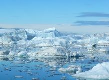 Iceberg Landscape. Large and small icebergs with small bits of ice in the mirror-like water - Greenland coast Royalty Free Stock Images