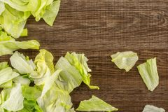 Fresh raw Iceberg Lettuce on brown wood. Iceberg lettuce table top isolated on brown wood background fresh torn salad leaves stack Royalty Free Stock Photos