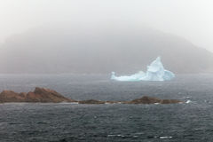 Iceberg melts near rocky shore hidden in misty fog. Melting iceberg in foggy foul weather off the coast of New Foundland, Canada stock photo