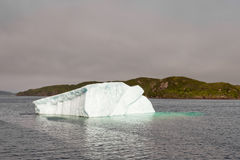 Iceberg melts in shallow coastal NL Canada water. Melting iceberg in coastal waters of Atlantic Ocean off Newfoundland, NL, Canada stock image
