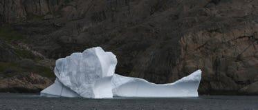 Iceberg in ocean. With cliffs in background, Denmark Strait, Greenland Stock Photo