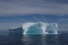 Iceberg off the coast of Greenland. Huge floating iceberg which has been naturally carved to form two arches stock photos