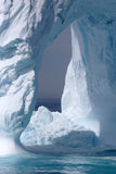 Iceberg off the coast of Greenland. Beautiful shaped iceberg with an arch naturally carved out of the center, floating off the coast of Greenland royalty free stock photography