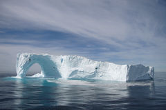 Iceberg off the coast of Greenland. Large iceberg floating off the coast of Greenland. The iceberg has a naturally formed arch on one side of the berg royalty free stock images