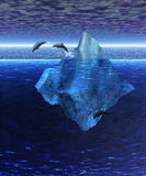 Iceberg in the Open Ocean with Pod of Dolphins Royalty Free Stock Photos