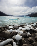 Iceberg Pieces on the Rocky Shore of a Cold Lake. Image of a blue, icy lake in El Chalten, Argentina, Large chunks of ice decorate the rocky shoreline royalty free stock photography