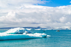 Iceberg and sightseeing boats in Jokulsarlon. A glacial river lagoon in southeast Iceland Stock Photos
