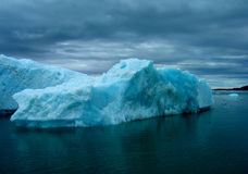 Iceberg in storm. Blue iceberg under stormy clouds Royalty Free Stock Photo