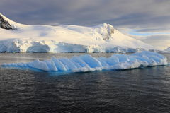 Iceberg in sunlight with landscape Stock Photography