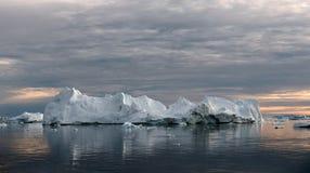 Iceberg at sunset. Nature and landscapes of Greenland. Disko bay. West Greenland. Iceberg floating in the water off the coast of Greenland. Nature and stock images