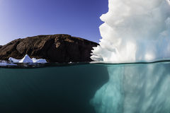 Iceberg Underwater. Underwater view of an iceberg off the east coast of Greenland. Red Island can be seen in the background, Scoresbysund fjord Greenland Royalty Free Stock Photos