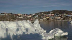 Iceberg vicino al piccolo villaggio nel mare di Groenlandia dalla piattaforma di un'imbarcazione da diporto nei raggi del tramont stock footage