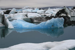 Icebergs. Blue white and black (lava) icebergs floating in calm water with reflections Royalty Free Stock Image