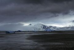 Icebergs below a mountain under stormy skies Royalty Free Stock Image