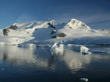 Icebergs, clear blue sky. Mirrored in ocean,Erreras Channel, Antarctica Stock Photo