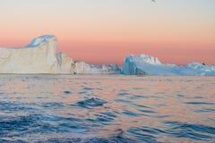 Icebergs dans le soleil de minuit, Ilulissat, Groenland Photos stock