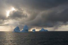 Icebergs et soleil derrière les nuages de neige Photos libres de droits