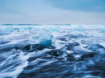 Icebergs floating on black volcanic beach, Iceland Royalty Free Stock Images