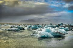 Icebergs floating in Jokulsarlon at sunset golden hour with glac Royalty Free Stock Photos